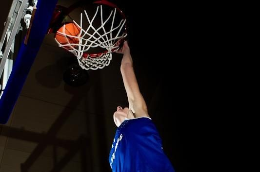 Aukštaūgė krepšininkė deda į krepšį iš viršaus