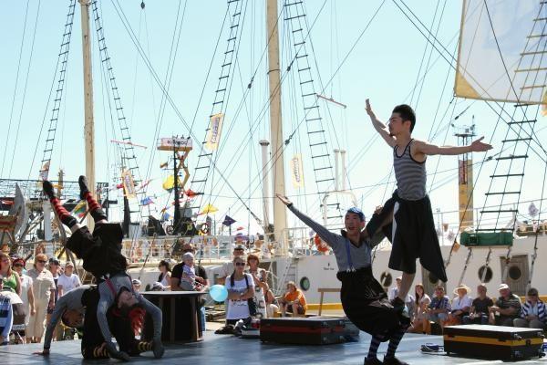 Cirko žmonės šėlioja su minia Jūros šventės dalyvių